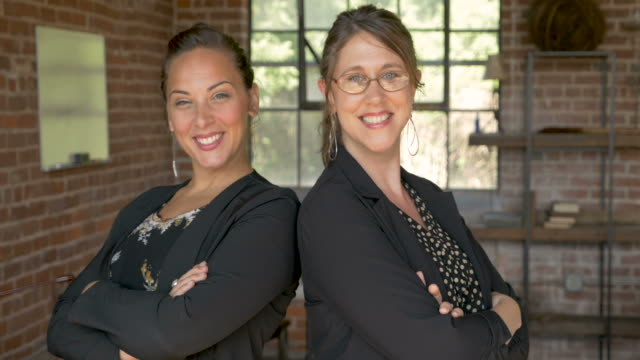 Two powerful attractive businesswoman standing back to back smiling Portrait of two beautiful powerful attractive businesswoman standing back to back smiling in a modern brick start up business setting back to back stock videos & royalty-free footage