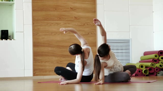 two pregnant young women doing relaxation exercise on exercise mat video