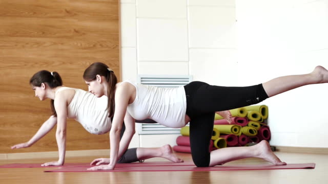 two pregnant young women doing relaxation exercise on exercising mat video