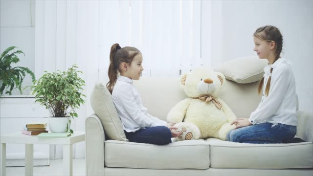 Two pretty girls sitting on the sofa, playing rock-paper-scissors to decide who will play with white soft bear.