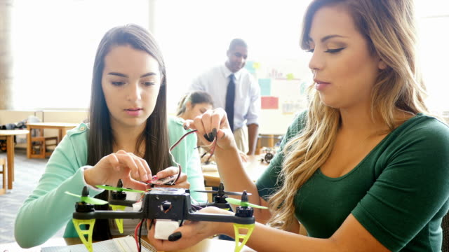 Two pretty Hispanic teenage girls work together to create robot at STEM school video