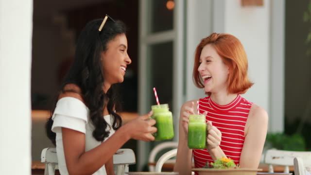 stockvideo's en b-roll-footage met twee mooie multi-etnische meisjes die en terwijl het drinken van gezonde groene sappen lachen en glimlachen - sapjes