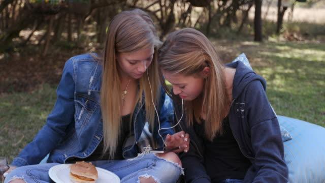 zwei hübsche junge mädchen im teenageralter anhören von musik auf ihrem handy und dem mittagessen in einem park - teenage friends sharing food stock-videos und b-roll-filmmaterial
