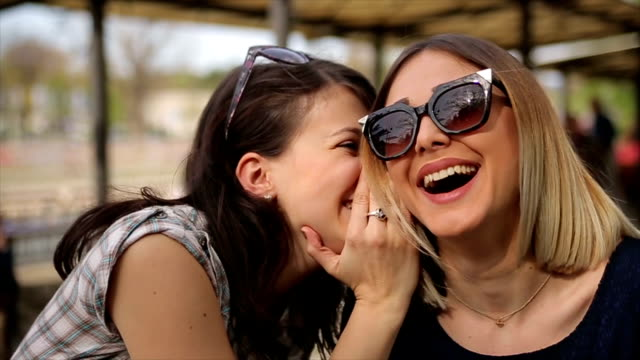 Two pretty young woman shares secrets, gossip. video