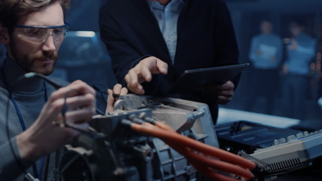 two professional automotive engineers with a tablet computer and inspection tools are having a conversation while testing an electric engine in a high tech laboratory with a concept car chassis. - ciągłość filmów i materiałów b-roll