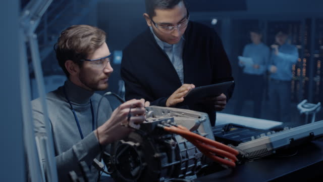 Video Two Professional Automotive Engineers with a Tablet Computer and Inspection Tools are Having a Conversation While Testing an Electric Engine in a High Tech Laboratory with a Concept Car Chassis.