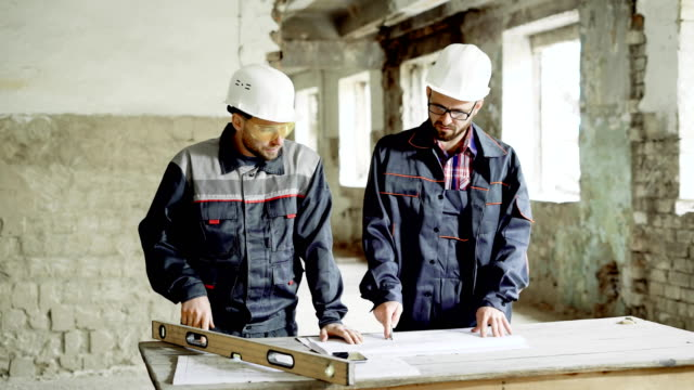 Two professional engineers working together at the desk with building documentation on construction area. Architect and foreman are standing on building site and investigating structural drawing of development video