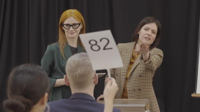 two professional female auctioneers calling out bids - asta oggetto creato dall'uomo video stock e b–roll