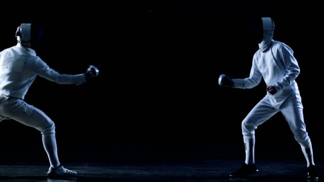 Two Professional Fencers Show Masterful Swordsmanship in their Foil Fight. One Fencer Recaptures Quick Fleche Attack. Shot Isolated on Black Background  with Cold Tones and Slow Motion. video