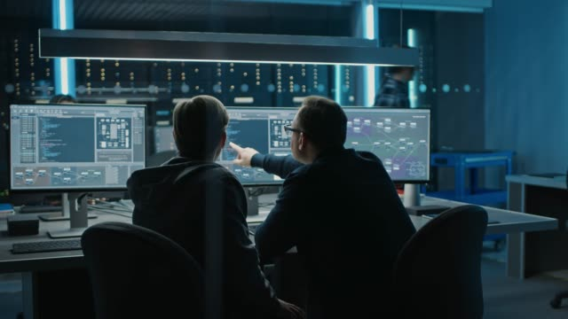 Two Professional IT Programers Discussing Blockchain Data Network Architecture Design and Development Shown on Desktop Computer Display. Working Data Center Technical Department with Server Racks Two Professional IT Programers Discussing Blockchain Data Network Architecture Design and Development Shown on Desktop Computer Display. Working Data Center Technical Department with Server Racks . Shot on RED EPIC-W 8K Helium Cinema Camera. blockchain stock videos & royalty-free footage