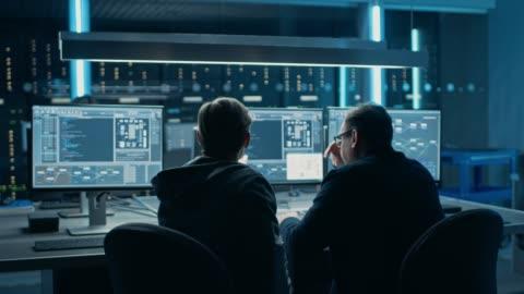 vídeos y material grabado en eventos de stock de dos programadores profesionales de ti discutiendo diseño y desarrollo de la arquitectura de redes de datos blockchain se muestra en la pantalla de computadora de escritorio. departamento técnico del centro de datos de trabajo con racks de servidores - codificar
