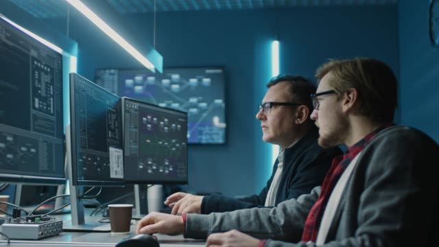 two professional it programers discussing blockchain data network architecture design and development shown on desktop computer display. working data center technical department with server racks - design filmów i materiałów b-roll