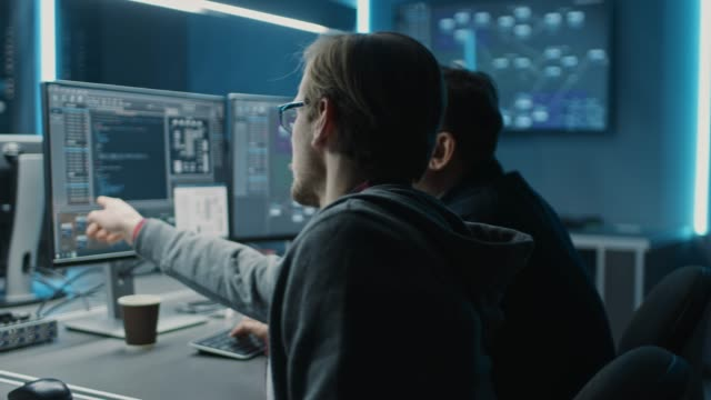 two professional it programers discussing blockchain data network architecture design and development shown on desktop computer display. working data center technical department with server racks - software video stock e b–roll