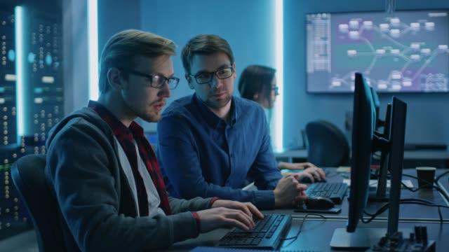 vídeos de stock, filmes e b-roll de dois profissionais it programers discutindo dados técnicos mostram na tela do computador desktop. departamento técnico do centro de dados de trabalho com racks de servidor em segundo plano - explicar