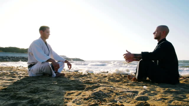 two professional karate fighters meditating on the beach sea background video