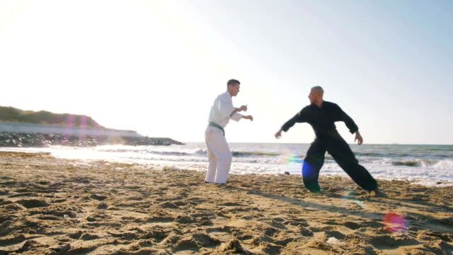two professional karate fighters on the beach sea background, slow motion video