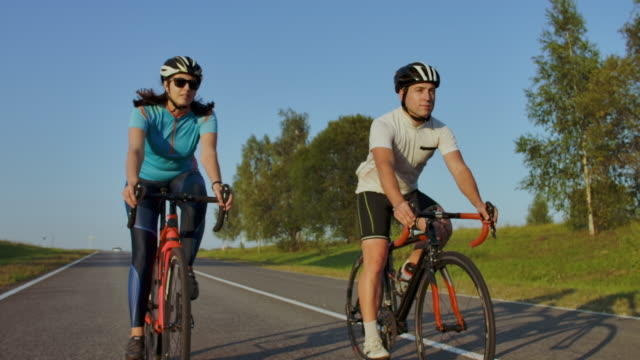 Two professional road cyclists ride their bikes on a hill. Hand held shot of two strong cyclists female and male on their training on a warm but windy summer day.