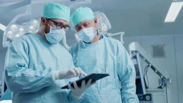 Dos profesionales cirujanos uso Digital Tablet PC mientras permanente en la sala de operaciones moderna del Hospital. - vídeo