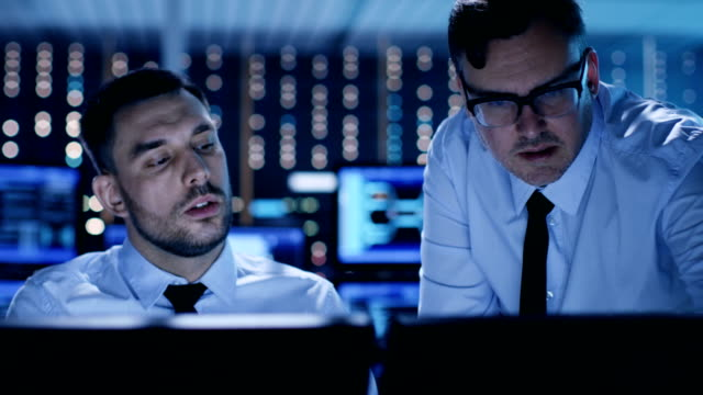 Two Professional Technicians Discussing Problems Shown on Multiple Monitors in a System Control Center. video