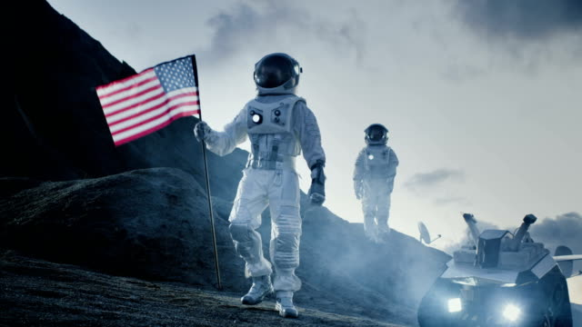 Two Proud Astronauts Plant American Flag on the Alien Planet. In the Background Research Base and Rover. video