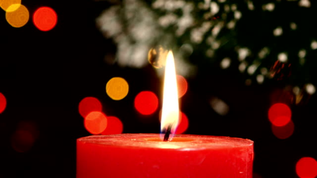 Two red candles with christmas decorations on black, bokeh, light, garland, cam moves to the right