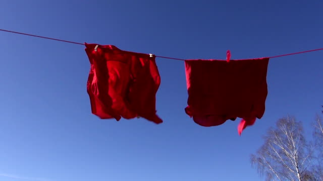 two red clothes shirts on string and wind video