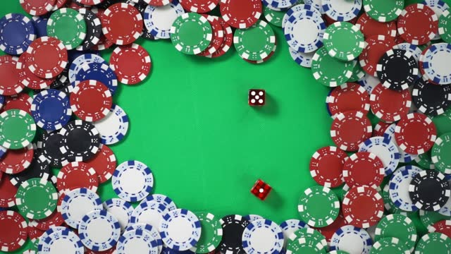 Two red dices are falling on a green table with poker chips in slow motion