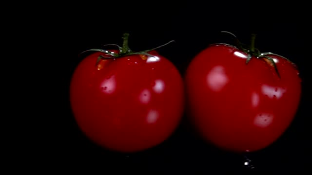 Two red juicy tomatoes are flying and colliding on the black background - video