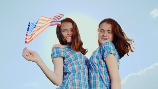 Two redheaded teenage girls with an American flag. Smile, look at the camera. 4K slow motion video video