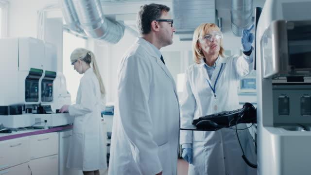 2 つのコンピューターのキーボードに科学者プログラムの開発医療機器を研究します。近代的な研究室で薬学研究を行う専門家のチーム - lab点の映像素材/bロール
