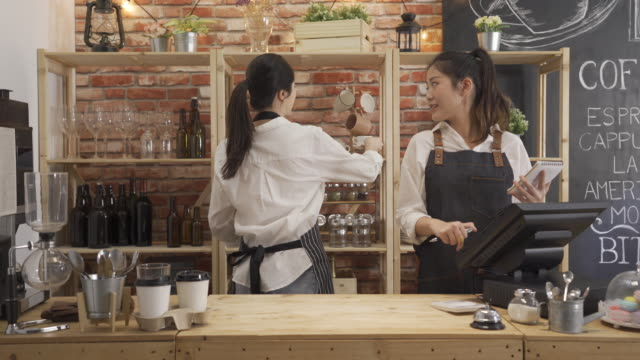 Two restaurant owners wear apron working in counter. women barista chatting while prepare coffee and taking customer order in cafe bar store. happy colleague relationship lifestyle concept. Two restaurant owners wear apron working in counter. women barista chatting while prepare coffee and taking customer order in cafe bar store. happy colleague relationship lifestyle concept. wait staff stock videos & royalty-free footage