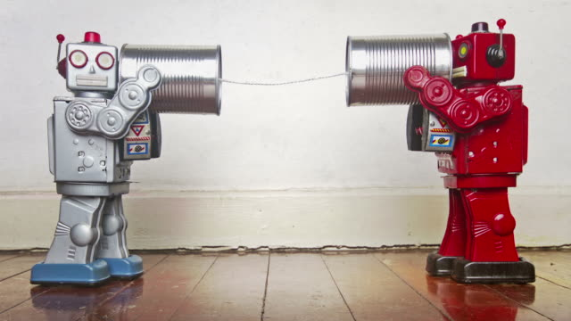 two retro robots on old tin can can phones