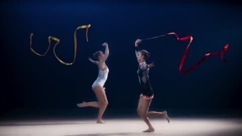 vidéos et rushes de slo mo speed ramp ld deux gymnastes rythmiques se déplaçant dans des directions opposées et effectuant un saut fractionné tout en tourbillonnant des rubans - exactitude