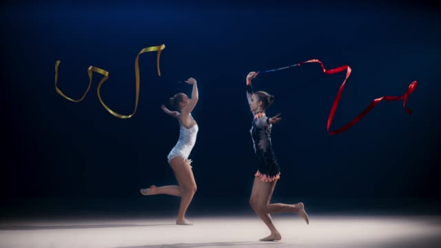 slo mo speed ramp ld two rhythmic gymnasts moving in opposite directions and performing a split leap while swirling ribbons - flessibilità video stock e b–roll