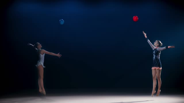 SLO MO LD Two rhythmic gymnasts moving in opposite directions and throwing their balls high in the air