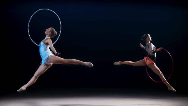 SLO MO SPEED RAMP LD Two rhythmic gymnasts moving opposite each other doing a split leap with a hoop Slow motion wide speed ramp locked down shot of two rhythmic gymnasts running across the floor opposite each other, rotating their hoops while performing a split leap. Shot in Slovenia. doing the splits stock videos & royalty-free footage