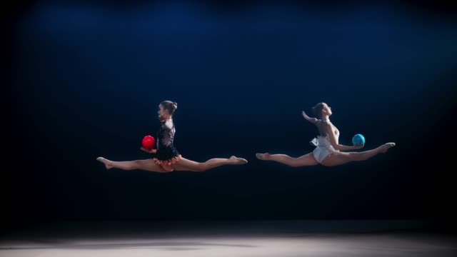 SLO MO Two rhythmic gymnasts opposite each other doing a split leap while throwing their balls into the air