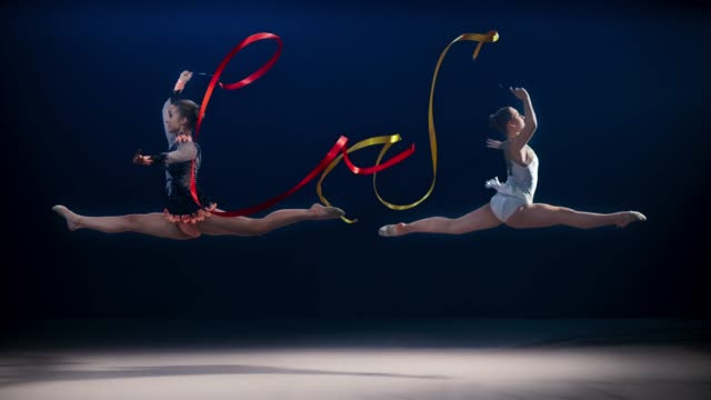 SLO MO Two rhythmic gymnasts opposite each other doing a split leap while swirling their ribbons