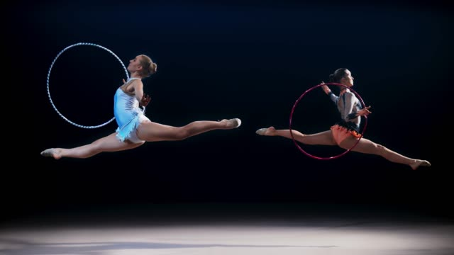 SLO MO Two rhythmic gymnasts opposite each other doing a split leap with a hoop
