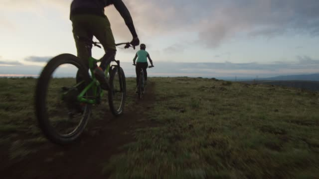 two riders (a female and a male) mountain bike in the rocky mountains west of denver, colorado at sunrise - percorso per bicicletta video stock e b–roll