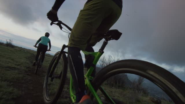 two riders (a female and a male) mountain bike in the rocky mountains west of denver, colorado at sunrise - bike tire tracks video stock e b–roll