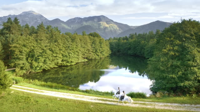 aerial two riders riding running horses on path along lake - attività equestre ricreativa video stock e b–roll