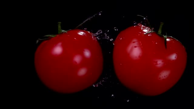 Two ripe red juicy tomatoes are flying and colliding on the black background - video