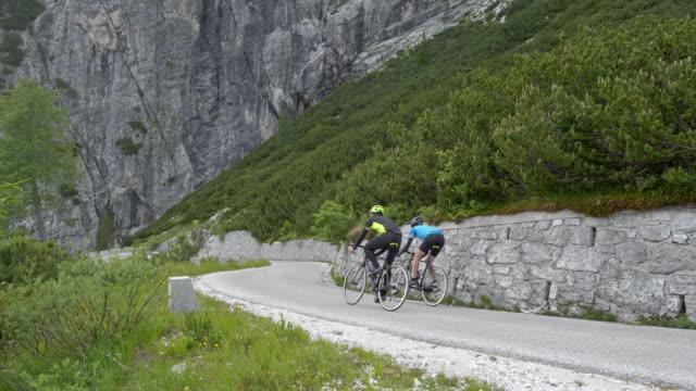 aerial two road cyclists descending a mountain road - ciclismo su strada video stock e b–roll