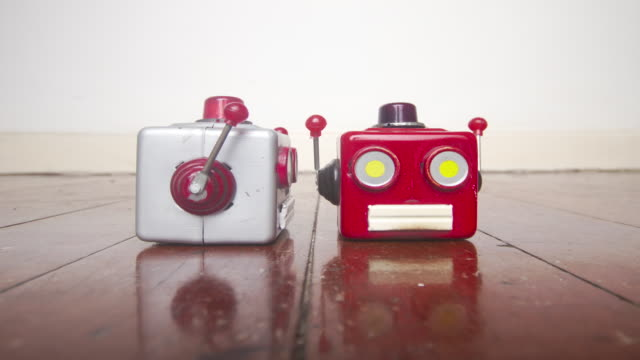 two robot head talking on old wooden floor
