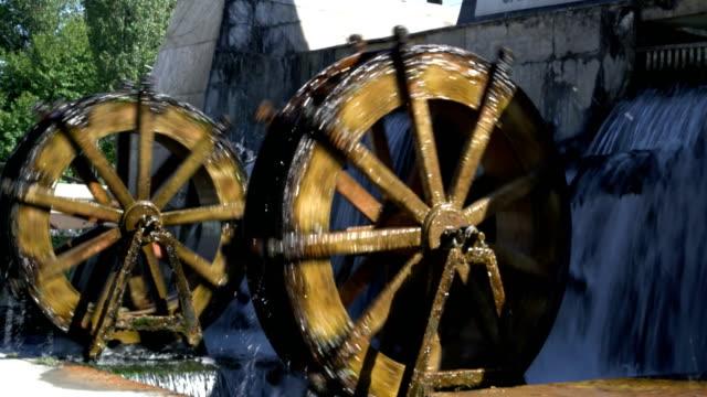 two rotating water mills 4k resulation - paesaggio collinare video stock e b–roll