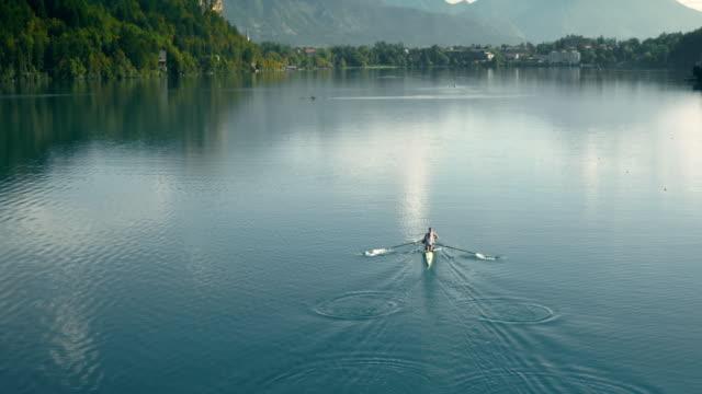 vídeos de stock, filmes e b-roll de antena dois remadores em um remo deslizando através de um belo lago - remo atividade física