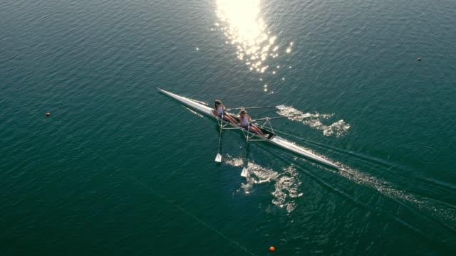 vídeos de stock, filmes e b-roll de antena dois remadores lemada um lago ensolarado em um double scull - remo esporte aquático