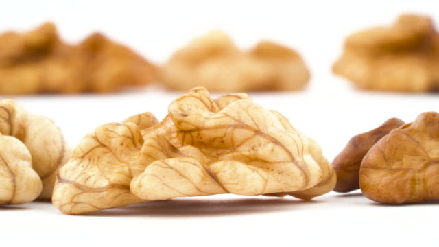 Two rows of walnuts without the shell are moving horizontally from one side of the frame to other. Isolated on the white background. Close-up. Macro.