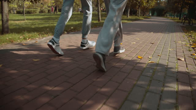 Two runners in sport shoes doing training in the park, regular healthy activity